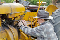 Farmer on the tractor fixing Stock Image