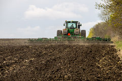 Farmer on tractor handles field on spring Royalty Free Stock Images