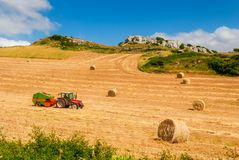 Farmer on Tractor making Hay Bales on Sardinian Countryside in Italy. Farmer on Tractor making Hay Bales on Countryside of Sardinia, Italy stock images