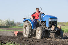 Farmer on the tractor. Man on blue tractor on blue sky background Royalty Free Stock Photography