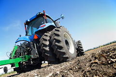 Farmer on a tractor plowed field Stock Images