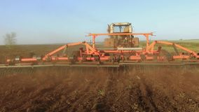 Farmer in tractor plows Russia steadicam motion agriculture soil the ground preparing land with seedbed cultivator as. Farmer in tractor plows Russia steadicam stock footage