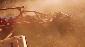 Farmer in tractor plows steadicam slow motion Russia agriculture soil the ground preparing land with seedbed cultivator. Farmer in tractor plows steadicam slow stock video footage