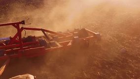 Farmer in tractor plows steadicam slow motion Russia agriculture soil the ground preparing land with seedbed cultivator. Farmer in tractor plows steadicam slow stock footage