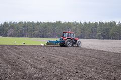 A farmer on a tractor prepares the land with a cultivator. Sowing on agricultural fields stock photos
