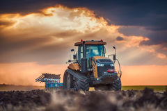 Farmer in tractor preparing land with cultivator Royalty Free Stock Image