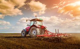 Farmer in tractor preparing land with seedbed cultivator. Royalty Free Stock Photo