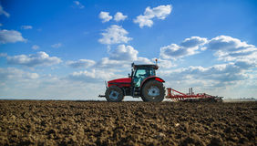 Farmer in tractor preparing land with seedbed cultivator. Royalty Free Stock Images