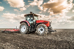 Farmer in tractor preparing land with seedbed cultivator. Stock Images