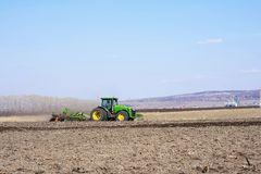 Farmer in tractor preparing land with seedbed cultivator as part of pre seeding activities in early spring season of agricultural stock photography