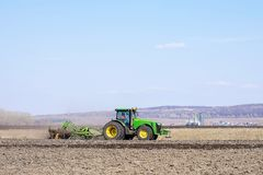 Farmer in tractor preparing land with seedbed cultivator royalty free stock image
