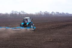 Farmer in tractor preparing land with seedbed cultivator royalty free stock photo