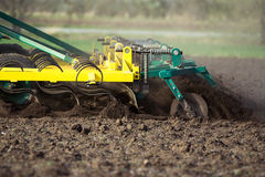Farmer in tractor preparing land with seedbed cultivator in early spring Royalty Free Stock Image