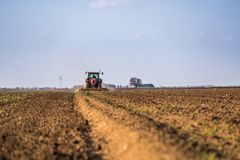 Farmer in tractor preparing land with seedbed cultivator royalty free stock photos