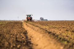 Farmer in tractor preparing land with seedbed cultivator royalty free stock photography