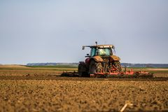 Farmer in tractor preparing land with seedbed cultivator stock images