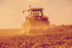 Farmer in tractor preparing land with seedbed cultivator. Filtered image Royalty Free Stock Image