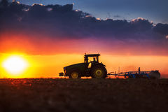 Farmer in tractor preparing land with seedbed cultivator Stock Photo