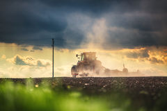 Farmer in tractor preparing land with seedbed cultivator Stock Photos