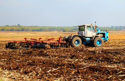 Farmer in tractor preparing land Stock Images