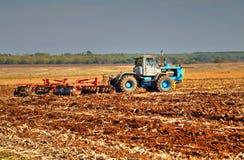 Farmer in tractor preparing land Stock Photos