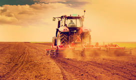 Farmer in tractor preparing land for sowing. Filtered image Royalty Free Stock Photo