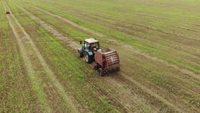 Aerial view of a tractor with a round baler which makes bales of straw on a harvested field, a concept of agribusiness stock footage
