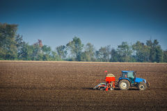 Farmer with tractor seeding crops in the field. Farmer with tractor seeding crops at field Royalty Free Stock Photo