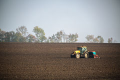Farmer with tractor seeding crops at field. Farmer with tractor seeding crops at the field Royalty Free Stock Image