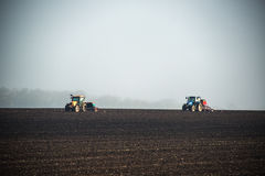 Farmer with tractor seeding crops at field. Farmers with tractors seeding crops at field Royalty Free Stock Photography