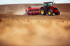 Farmer with tractor seeding crops at field Royalty Free Stock Photo