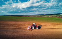 Farmer with tractor seeding crops at field stock photo