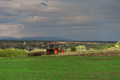Farmer with tractor seeding crops at field. In spring Stock Image