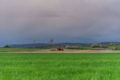 Farmer with tractor seeding crops at field. In spring Stock Photos