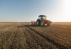 Farmer with tractor seeding - sowing crops at agricultural field Royalty Free Stock Photography