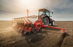 Farmer with tractor seeding sowing crops at agricultural field royalty free stock images