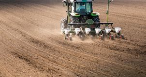 Farmer with tractor seeding sowing crops at agricultural field royalty free stock image