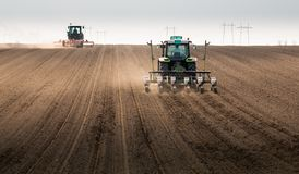 Farmer with tractor seeding sowing crops at agricultural field royalty free stock photography