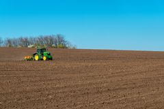 Farmer with tractor seeding - sowing crops at agricultural field. S in spring. Selective focus, copy space Stock Image