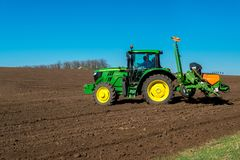 Farmer with tractor seeding - sowing crops at agricultural field. S in spring. Selective focus, copy space Royalty Free Stock Photos