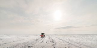 Farmer with tractor seeding - sowing crops at agricultural field. S in winter - snow Royalty Free Stock Photo