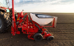 Farmer with tractor seeding - sowing crops at agricultural field Stock Image