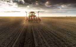 Farmer with tractor seeding - sowing crops at agricultural field. S in spring Royalty Free Stock Images