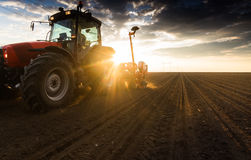 Farmer with tractor seeding - sowing crops at agricultural field. S in spring Royalty Free Stock Image