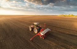 Farmer with tractor seeding - sowing crops at agricultural field Royalty Free Stock Images