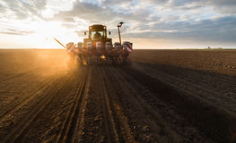 Farmer with tractor seeding - sowing crops at agricultural field. S in spring Stock Photos