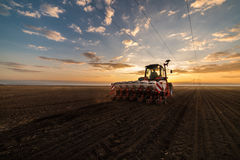 Farmer with tractor seeding - sowing crops at agricultural field. S in spring Royalty Free Stock Photos