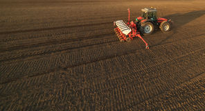 Farmer with tractor seeding - sowing crops at agricultural field. S in spring Stock Photography