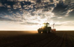 Farmer with tractor seeding - sowing crops at agricultural field Stock Photography
