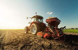 Farmer with tractor seeding - sowing crops at agricultural field. S in spring Stock Photo